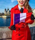 woman on embankment near Notre Dame de Paris showing flag