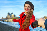 traveller woman holding friends hand and pointing at Notre Dame