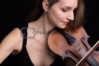 beautiful woman playing violin studio portrait on black