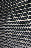 large stack of wine bottles in winery