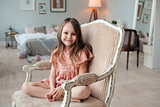 Portrait of a cute little girl sitting in the chair in her room