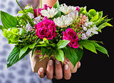female hands holding gift and vintage wedding bouquet of rose