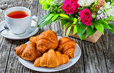 croissants, tea and flowers on an old wooden table