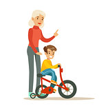 Grandmother Teaching Boy To Ride Bicycle, Part Of Grandparents Having Fun With Grandchildren Series