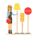Woman Choosing A Living Room Lamp, Smiling Shopper In Furniture Shop Shopping For House Decor Elements