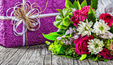 bouquet of fresh flowers and gift box on wooden table