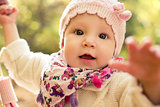 Closeup portrait of beautiful baby girl wearing stylish hat and cozy sweater. Outdoors spring, autumn photo.
