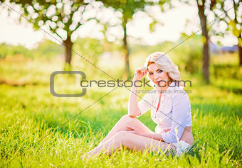 Smiling beautiful young girl sitting on grass in garden