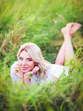 Smiling beautiful young woman lying among green grass