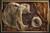Linen bag with coffee grains, a hank of a cord, a stick of cinnamon, berry of a juniper and fruits of an anisetree on a tray from a bamboo