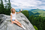 woman hiker taking photo with cellphone on mountain top