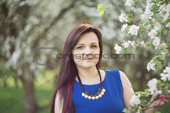 beautiful young brunette woman standing near the blossoming apple tree on a warm spring day