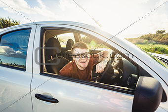 Attractive young man showing his new car keys and smiling