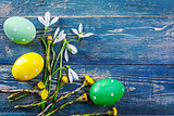 Easter eggs and spring flower snowdrop on old wooden blue