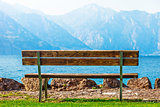 Wooden bench at coast of lake with blue mountains