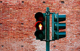 Green traffic light with burning yellow lamp