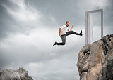 Businessman jumping over the mountains to reach a door