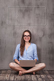 Young smiling woman sitting on the wooden floor with laptop