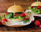 Homemade traditional burgers with beef,radish,lettuce, served on wooden background.