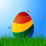 Curved striped Easter egg on grass over blue sky