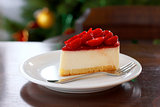 Fresh strawberry cheesecake. Selective Focus on the front upper edge of cake. Christmas tree in background