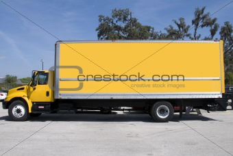 A yellow box delivery truck with blue sky