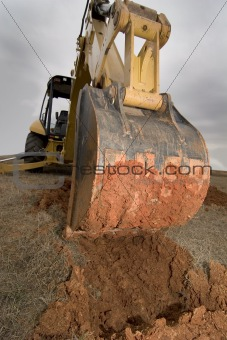 Backhoe digging in red dirt.