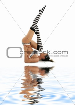 striped underwear supported shoulderstand on white sand