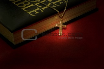 A gold cross necklace on a holy Bible