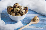 Quail eggs in bowl wooden spoon and gauze