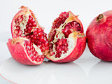 Ripe pomegranate fruit on a wite porcelain plate