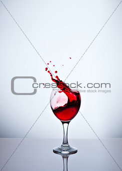 A glass with red wine and sprays.