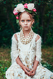 Portrait of a little girl with wreath of peony flowers