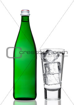 Green bottle of sparkling mineral water with glass