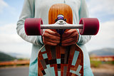 hands with longboard closeup