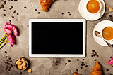 Tablet, coffee and croissants