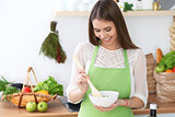 Young happy woman is cooking or eating fresh salad in the kitchen. Food and health concept