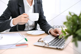 Close up of business woman hands with a cup of coffee is sitting at the table and typing on a laptop computer in the white colored office