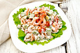 Salad with shrimp and tomatoes in plate on board