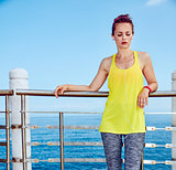 Healthy woman in fitness outfit listening to music at embankment