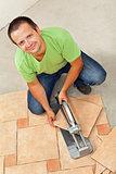 Man laying ceramic floor tiles - cutting one piece