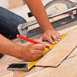 Laying ceramic floor tiles - man hands marking tile to be cut, c