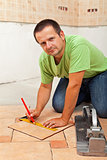 Man laying ceramic floor tiles - measuring and cutting one piece