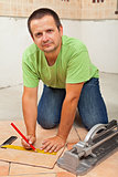 Man laying ceramic floor tiles in a new building