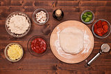 Phases of making a pizza - stretching the dough on wooden plate