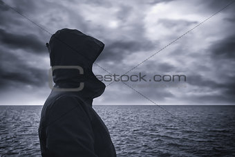 Faceless hooded person looking at horizon over sea water