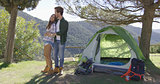 Loving couple kissing near tent