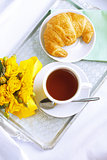 Morning breakfast with croissant and tea.