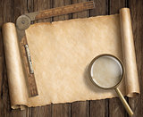 vintage loupe on table with treasure map scroll and ruler