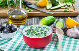 Tzatziki sauce, cucumber, bottle of olive oil on a green napkin